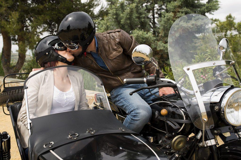Casal de homem e mulher se beijando na boca. Ambos estão de capacete preto, óculos e sentados sobre uma moto.