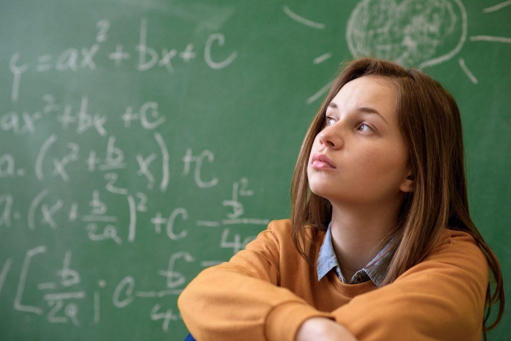 menina jovem, no ensino médio, sentada em frente de lousa.