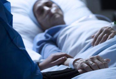 Pessoa dormindo em cama de hospital, e outra pessoa repousa a mão em seu braço.