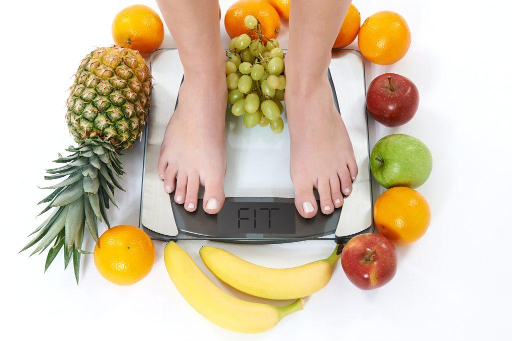 Pés femininos sobre uma balança de peso na cor branca. Em volta da balança, vários tipos de frutas como banana, laranja, abacaxi, uva e maças.