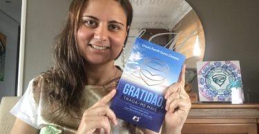 Autora segurando seu livro