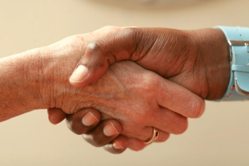 Aperto de mãos entre um homem e uma mulher.