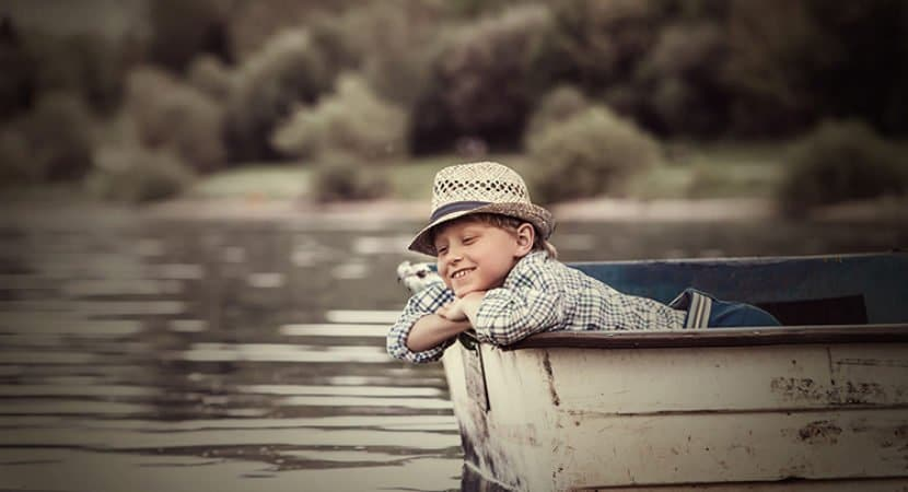 Imagem de um lago com um barquinho. Nesse barquinho um menino pensativo. Ele está vestindo uma camisa xadrez e um chapéu de palha.