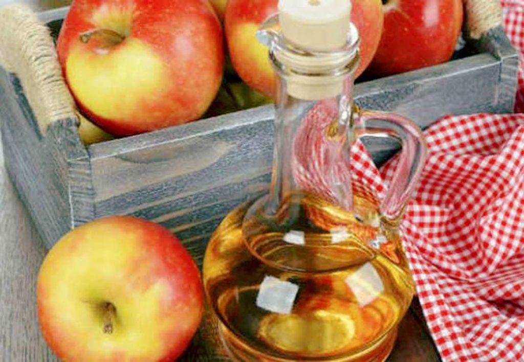 Vinagre de maça dentro de uma jarra de vidro. Ele está sobre uma mesa de madeira. Ao lado uma caixa  cheia de maças vermelhas e uma toalha quadriculada nas cores vermelho e branco.