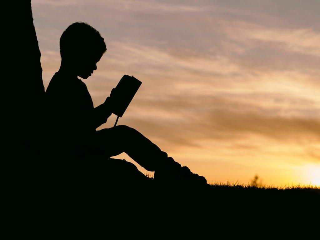 Silhueta de criança lendo livro com pôr-do-sol ao fundo