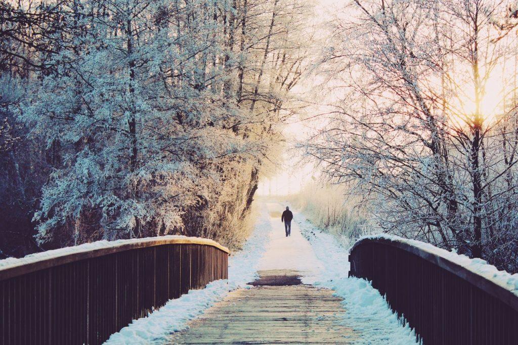Homem visto de costas após atravessar uma ponte em paisagem de inverno.