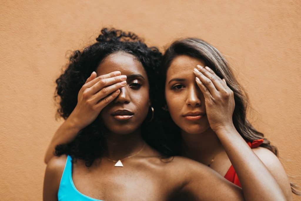 Duas mulheres com as mãos nos olhos uma da outra