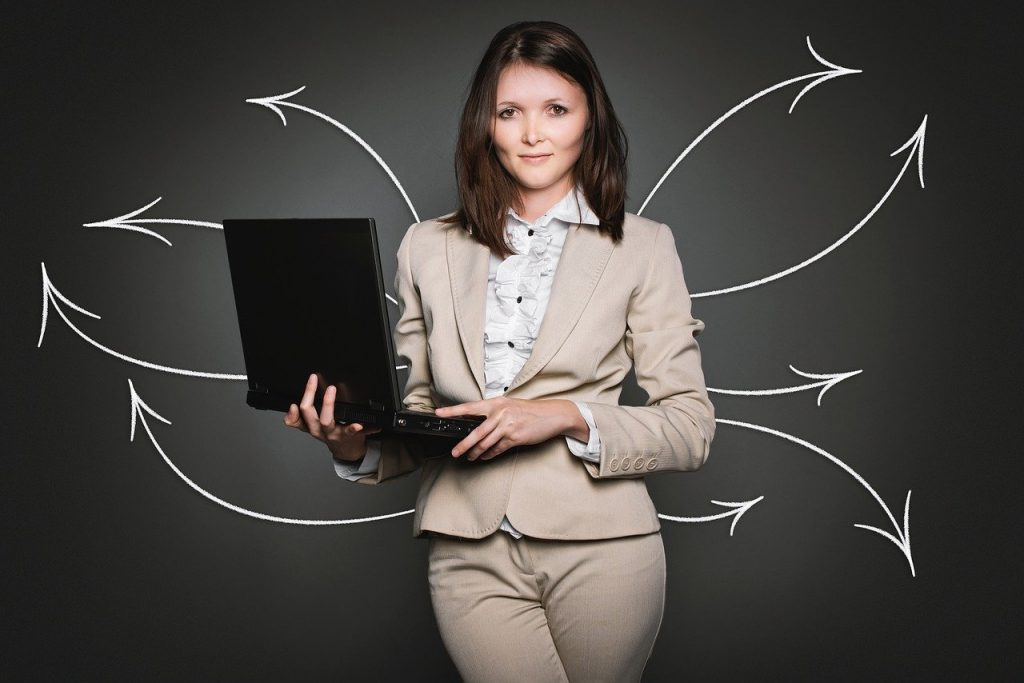 Mulher com roupas sociais segurando um notebook. Ao fundo, setas brancas partem de trás da mulher e saem em diferentes direções.