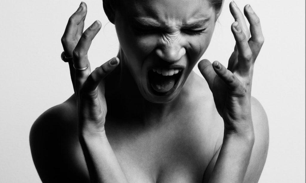 Imagem em preto e branco de uma mulher nervosa com as duas mãos sobre o rosto. Ela está gritando.