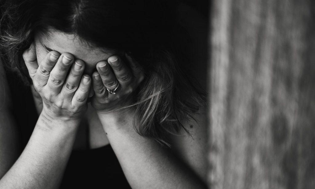 Imagem em preto e branco de uma mulher com as duas mãos sobre os olhos. Ela se encontra cabisbaixa.