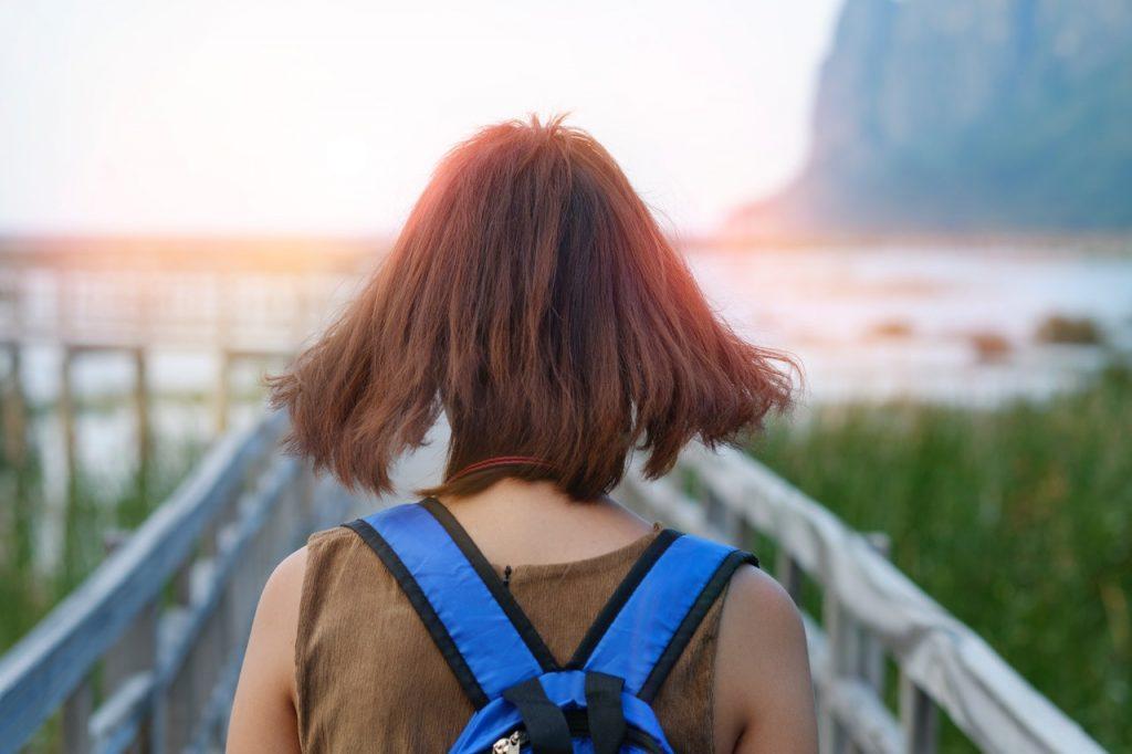 Mulher de cabelos curtos vista de costas em frente a uma ponte e uma paisagem natural.
