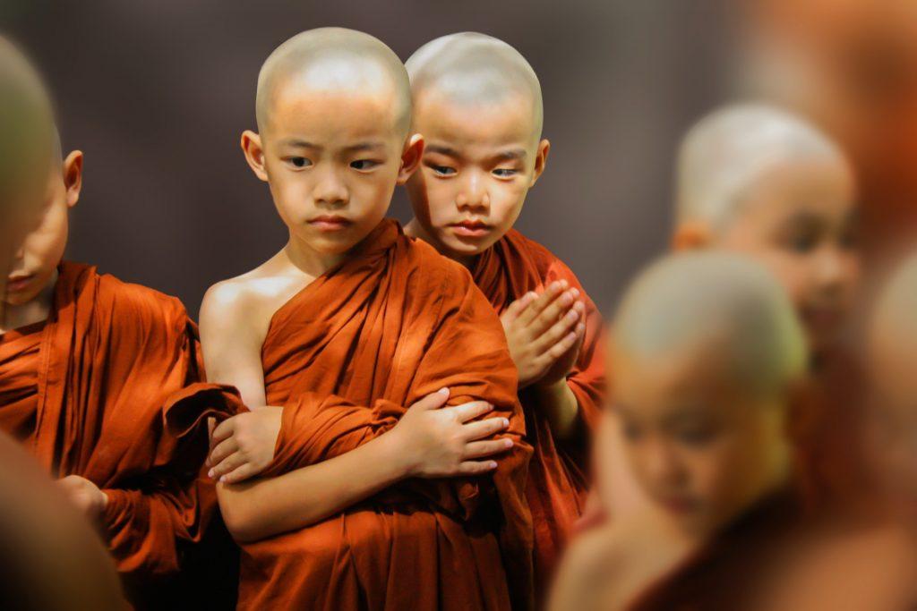 Crianças budistas com vestimenta tradicional laranja.