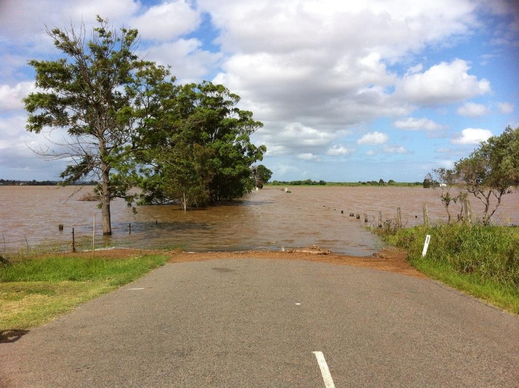 Rua alagada por água suja de barro onde seria uma estrada de terra.