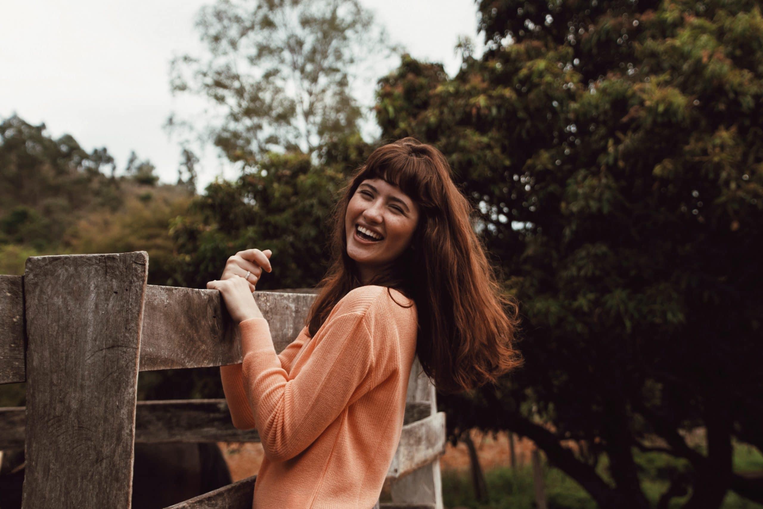 Menina em cerca de madeira sorrindo
