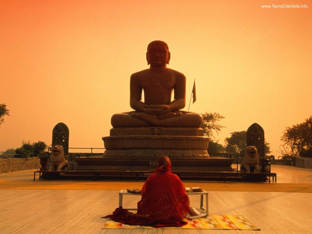 Praticante do budismoo sentando em um tapete, de frente para a estátua de Buda. Eles estão em um espaço aberto e bem iluminado.