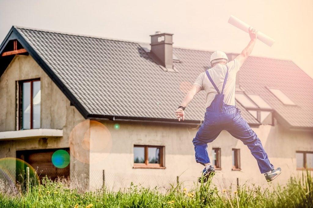 Trabalhador de construção pula de felicidade em frente a obra construída.