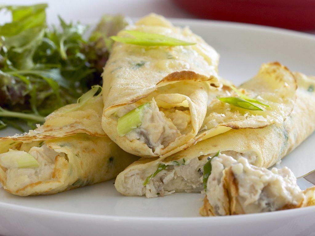 Três crepiocas prontas para serem servidas. Estão sobre um prato branco e de acompanhamento salada verde.
