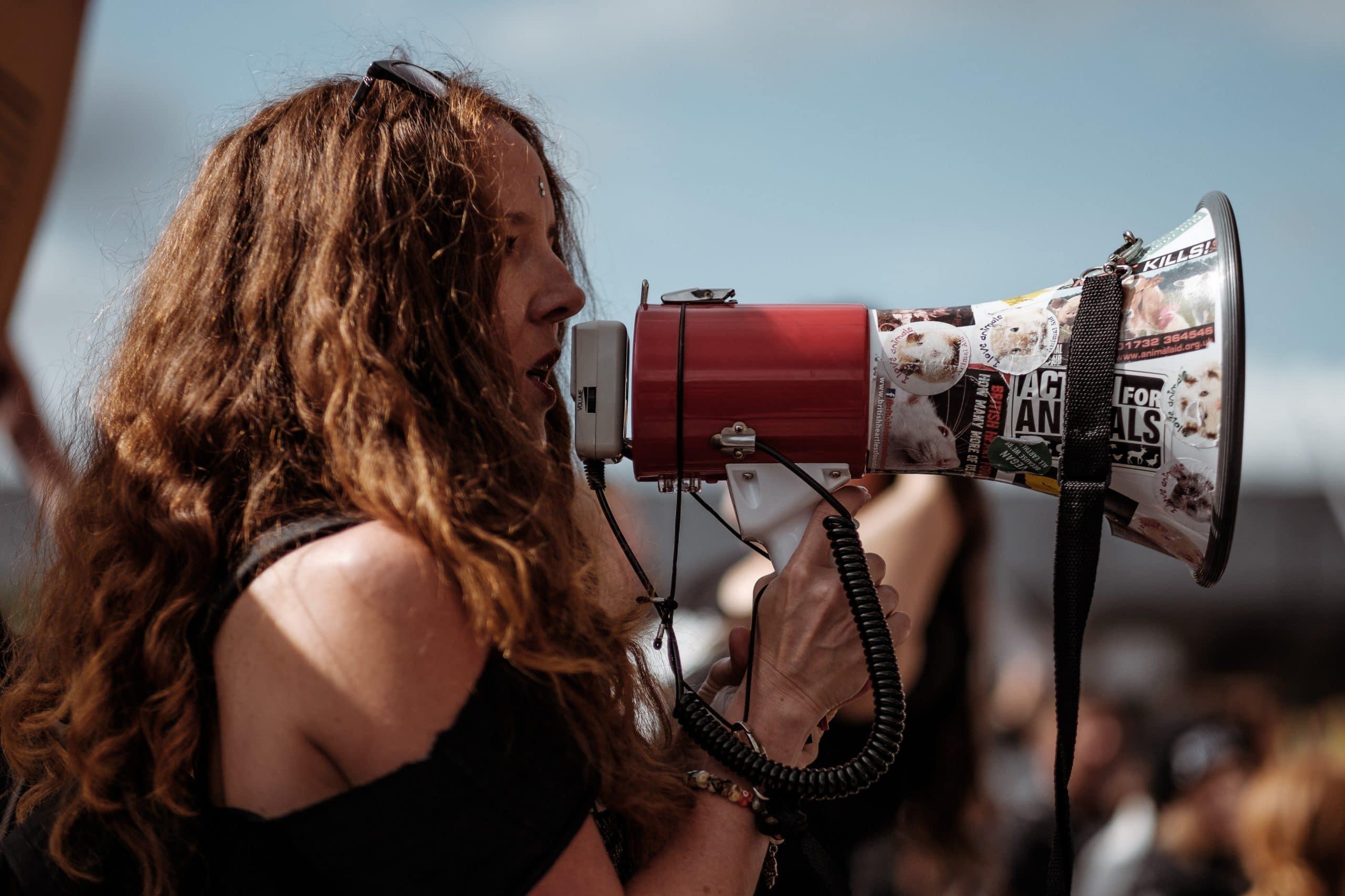 Mulher de perfil segurando megafone