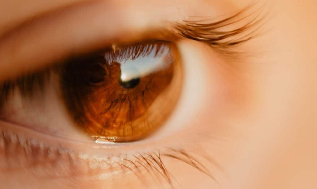 Foto ampliada de um olho castanho com aspecto triste.