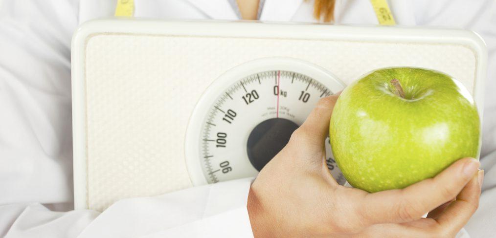 Mão de uma médica segurando uma balando de peso na cor branca e também uma maçã verde.