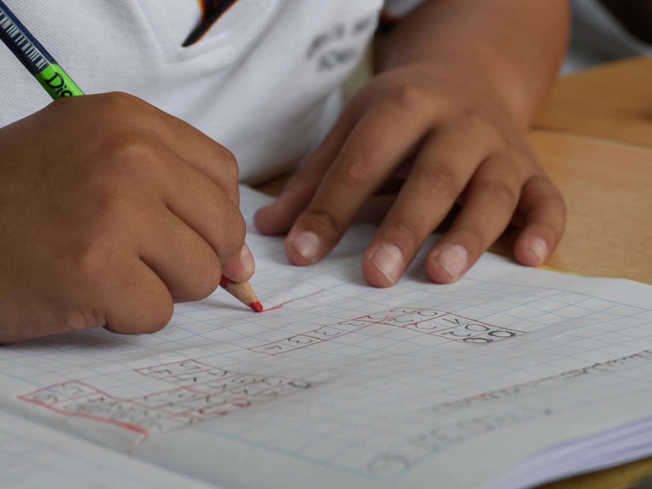Mãos de criança escrevendo em caderno
