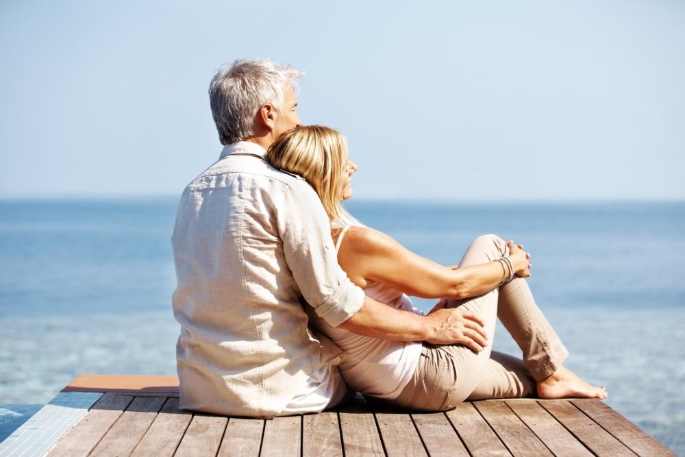 Casal de homem e mulher, destindo roupas claras, sentados sobre o pier, apreciando o azul do mar.