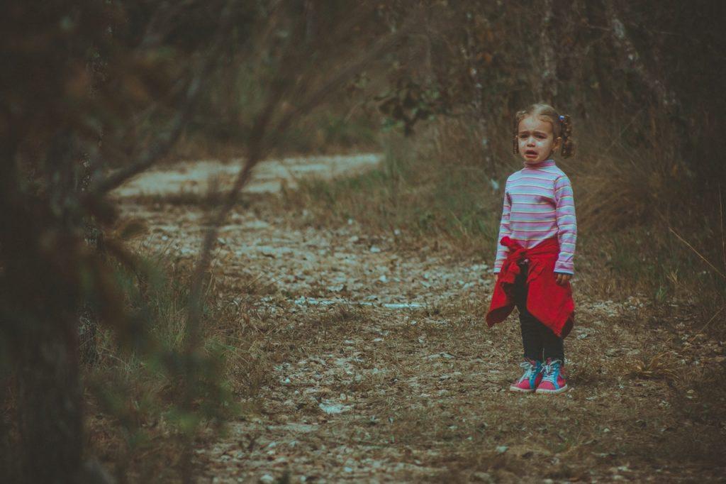 Menina pequena sozinha em floresta, chorando.