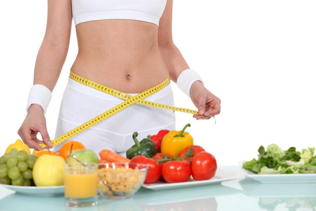Mulher com corpo escultural. Está de top, bermuda e munhequeira branca e usando uma fita métrica em torno de sua cintura. À sua frente, três pratos com frutas, legumes e verduras, um copo com suco de laranja.
