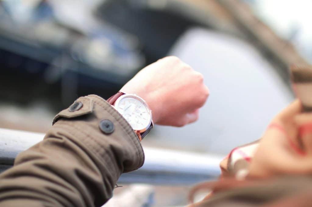 Imagem ampliada de uma pessoa olhando para o relógio com fundo desfocado.