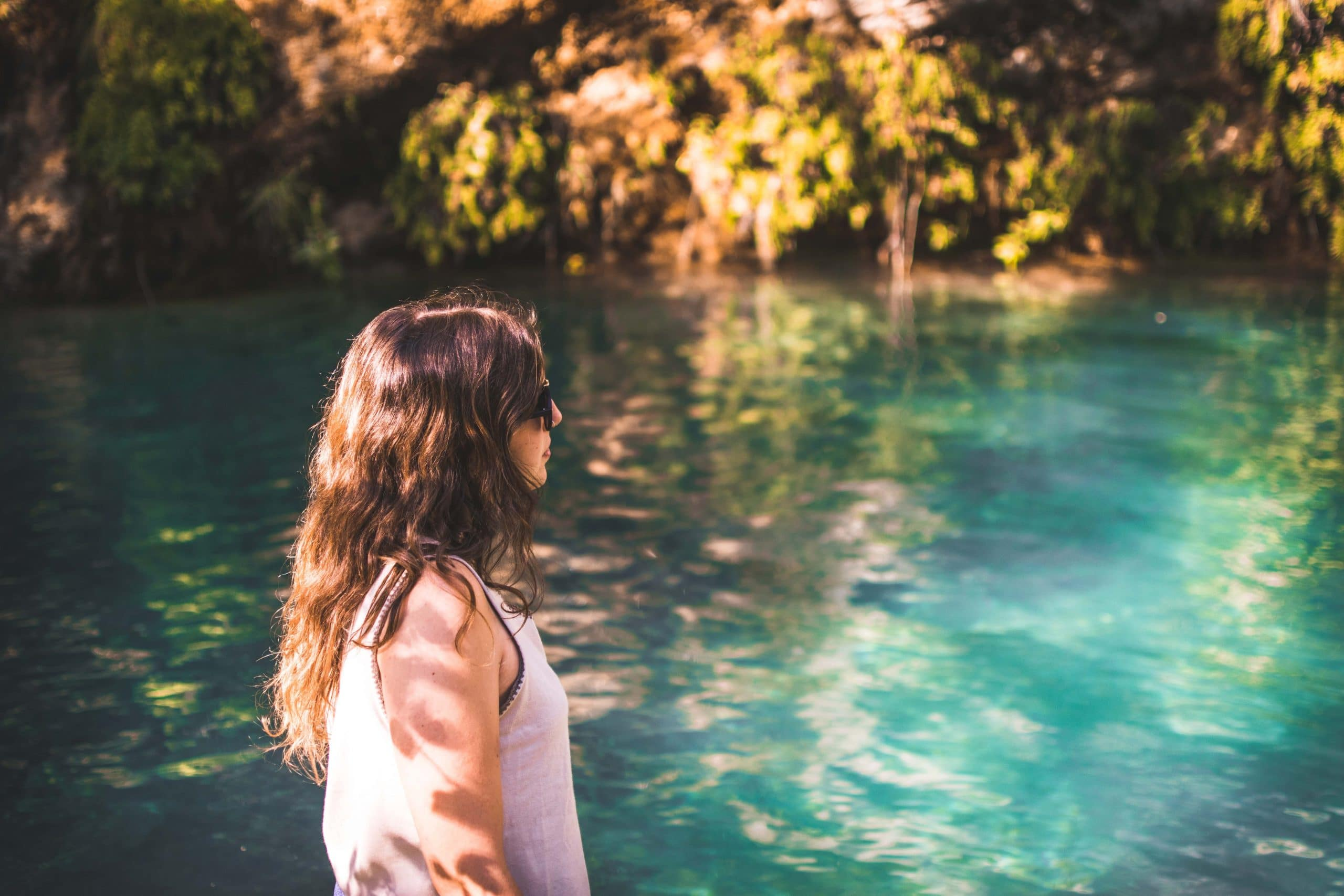 Mulher ao lado de um lago.