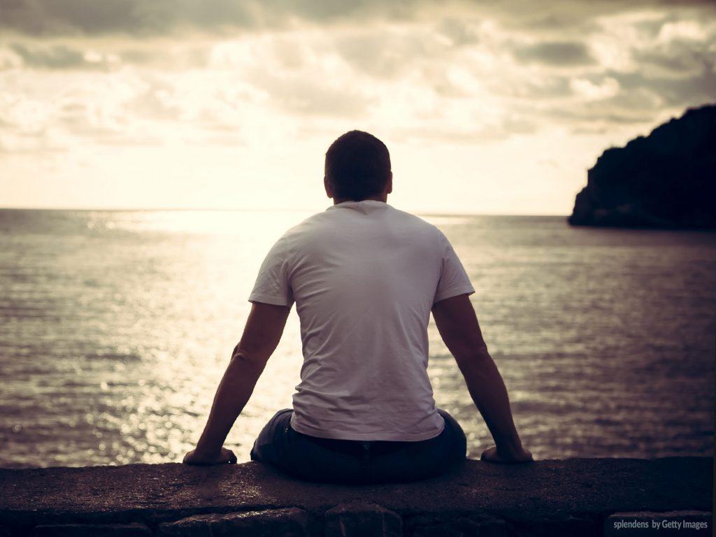 Homem sentado sobre uma muralha de pedra olhando para o infinito do mar, tendo ao fundo o por do sol. Ele está usando uma camiseta na cor branca e uma calça jeans.