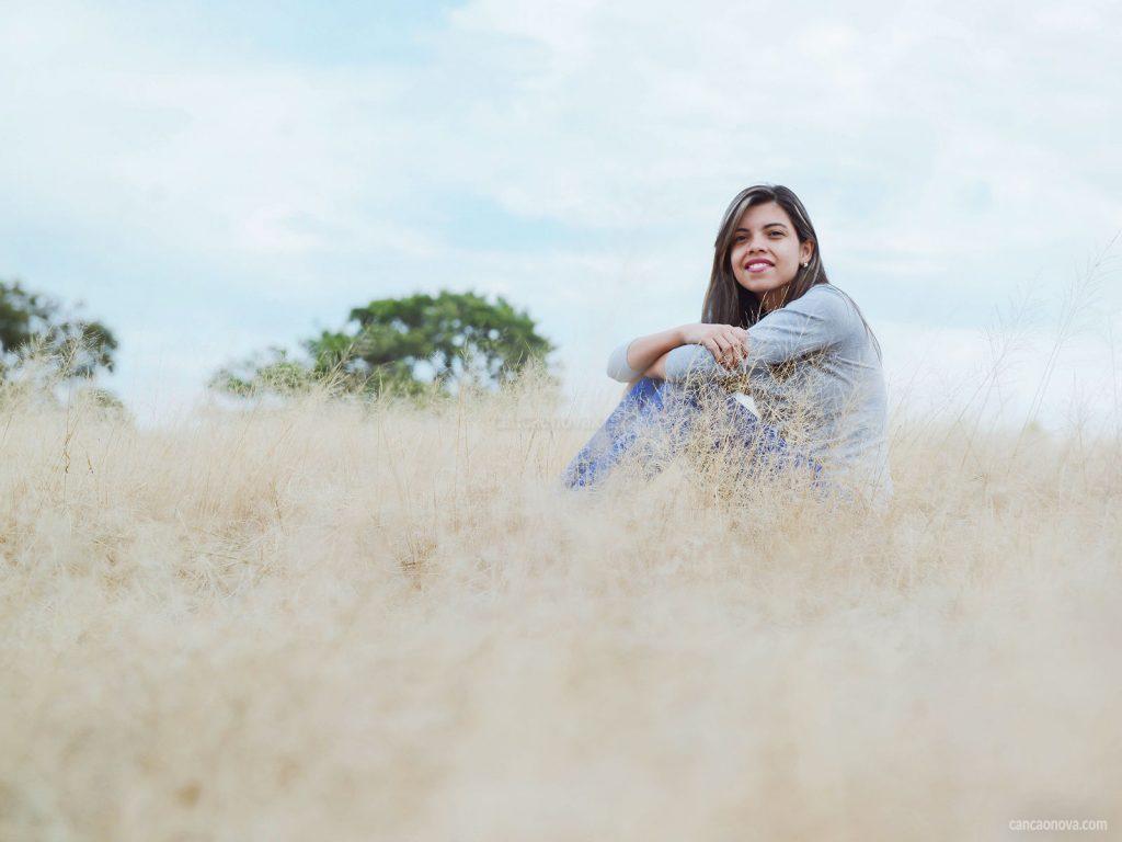 Mulher sorrindo em um campo de algodão. Ela está sentada e ao fundo da paisagem temos duas copas de árvores na cor verde.