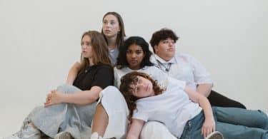Mulheres sentadas no chão uma ao lado da outra
