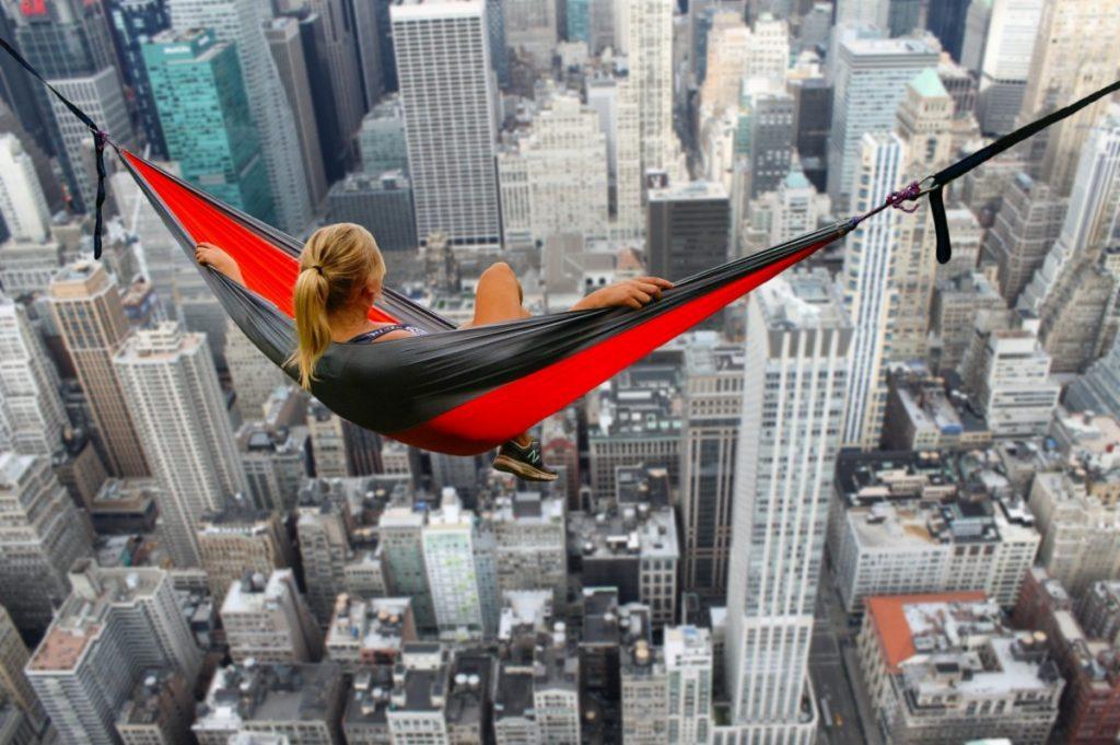 Mulher sentada em rede muito alta sob prédios em cidade grande.