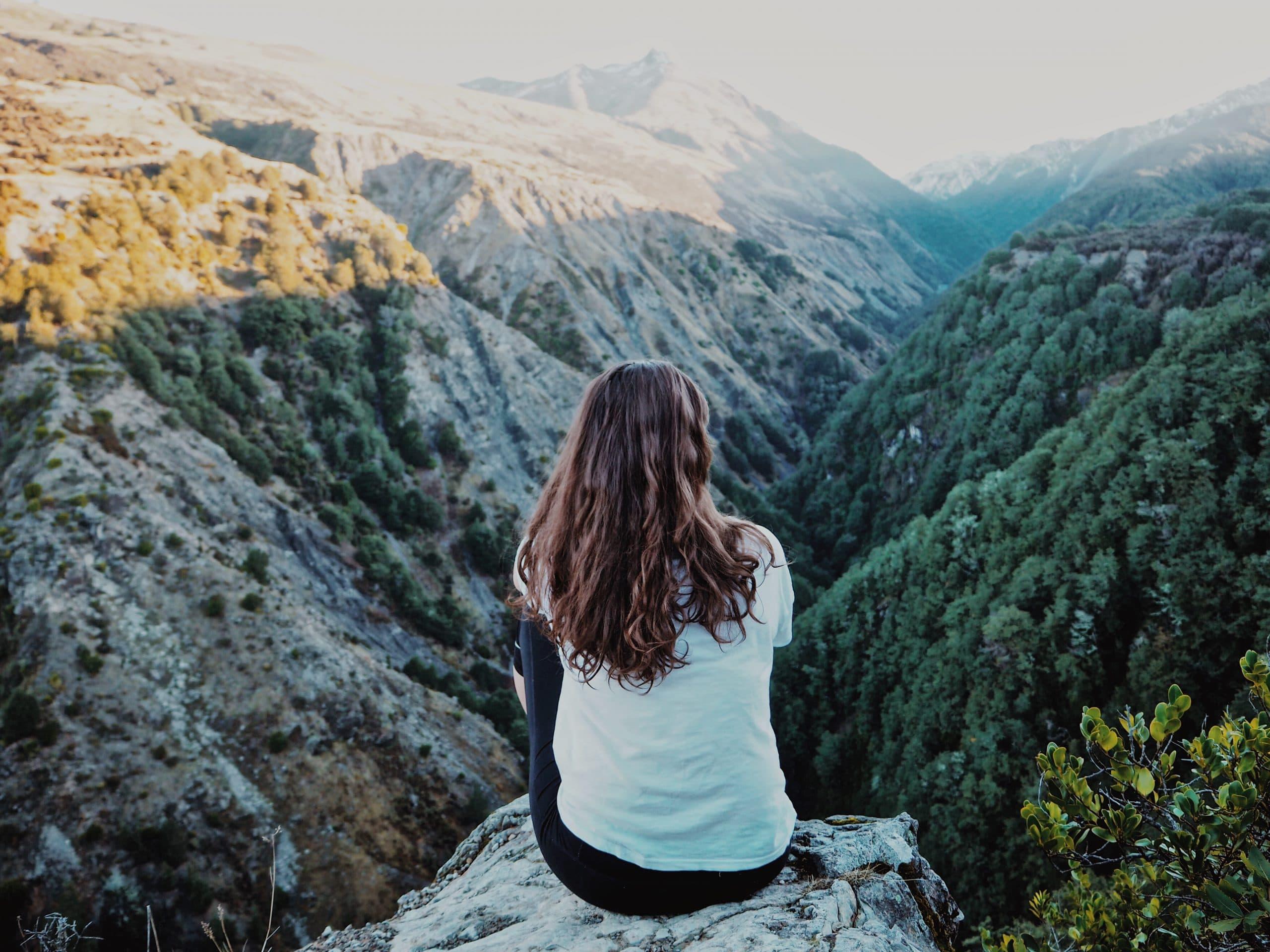 Mulher sentada de costas em montanha