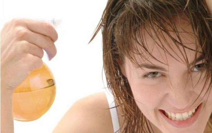 Mulher sorrindo com os cabelos molhados segurando em uma de suas mãos um borrifador de água, que no caso, está com vinagre de maça.