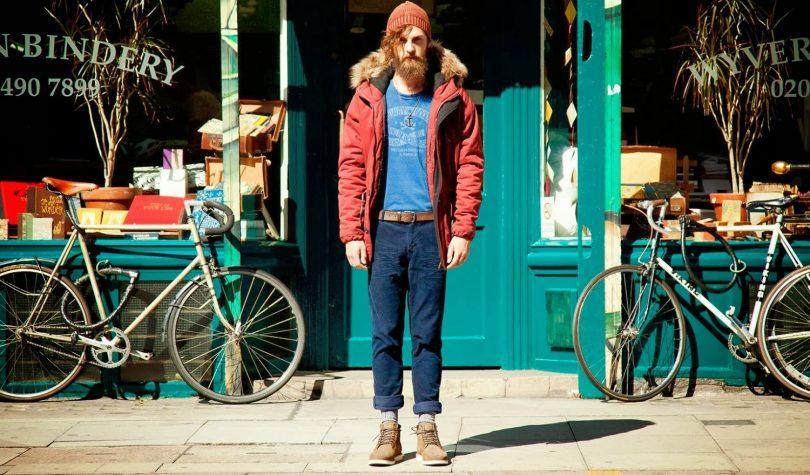 Homem usando uma jaqueta e touca na cor marrom. Para complementar o look hipster, calça jeans e camiseta azul. Ao fundo, uma loka e duas bicicletas compõem o cenario.