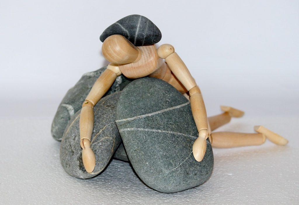 Boneco de madeira imobilizado por pedras acinzentadas.
