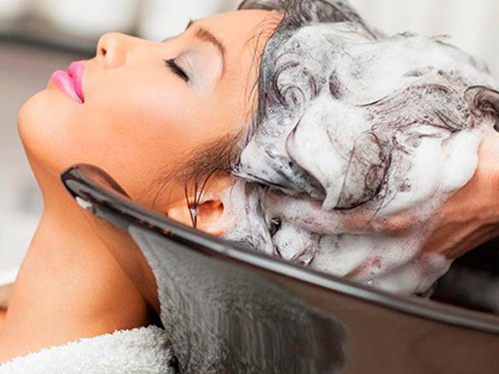 Mulher cpm a cabeça inclinada em um lavatório. Os seus cabelos estão sendo ensaboados pelas mãos de uma cabelereira.