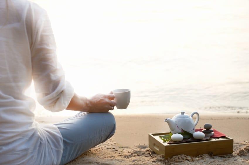 Imagem de metade do corpo de uma mulher. Ela veste uma camisa branca e calça azul clara. Está em posição de meditação, olhando para o mar. Em uma das mãos segura uma xícara de café. Ao seu lado, uma bandeja com um bule branco.