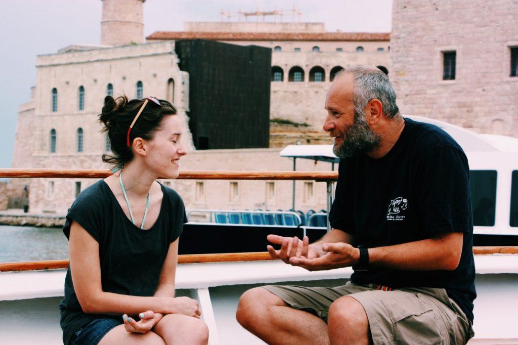 Um homem mais velho e uma mulher estão sentados em um barco, conversando em frente a um rio.