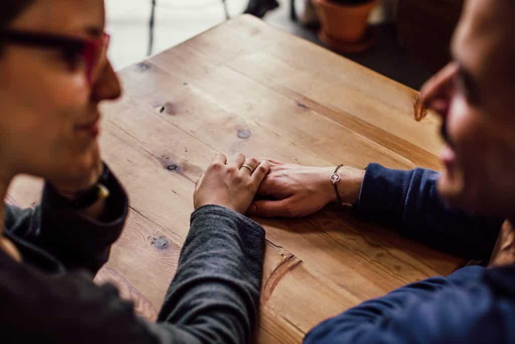 Duas pessoas de mãos dadas em uma mesa, conversando.