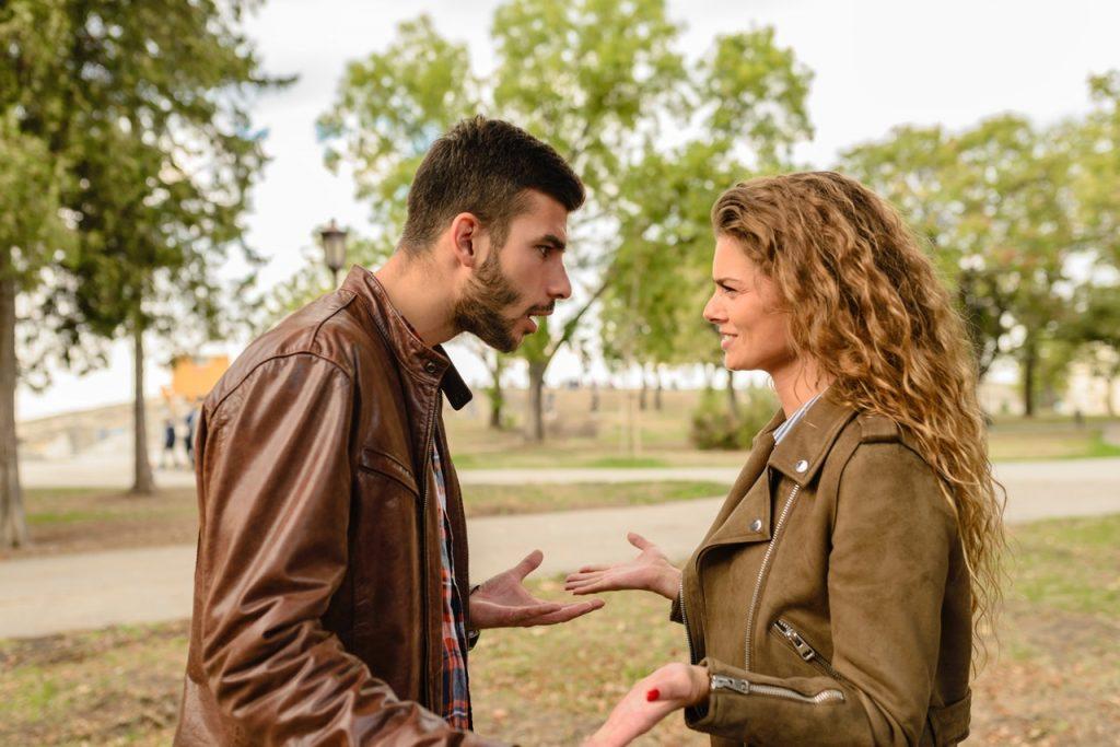Homem e mulher discutindo entre si em um parque.