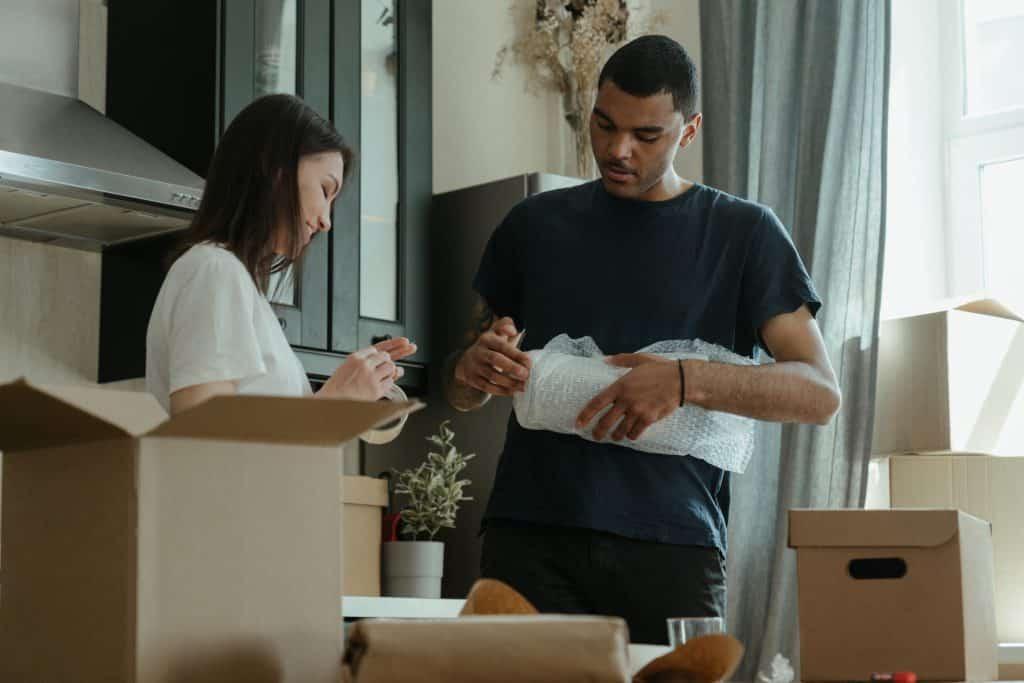 Homem e mulher empacotando as coisas da casa para a mudança.