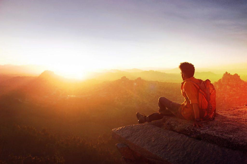 Homem sentado na beirada de uma montanha, observando o pôr do sol.