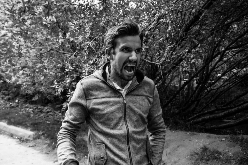 Foto em preto e branco de homem com a boca aberta e a expressão de quem está gritando.