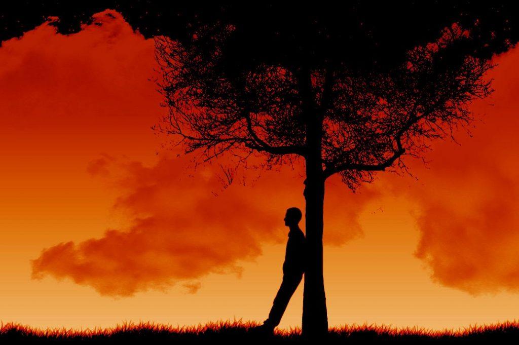 Imagem de um homem encostado em uma árvore. Ele está em um campo aberto. A imagem tem uma cor avermelhada.