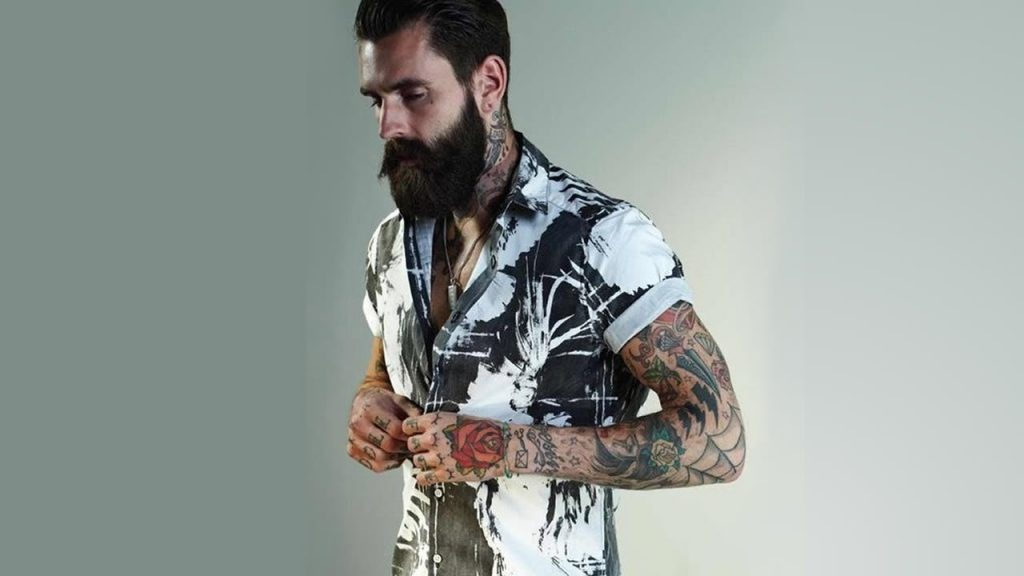 Homem com barba e bigode pretos, braços tatuados, abotoando uma camisa branca com estampas na cor preta, de manga curta.