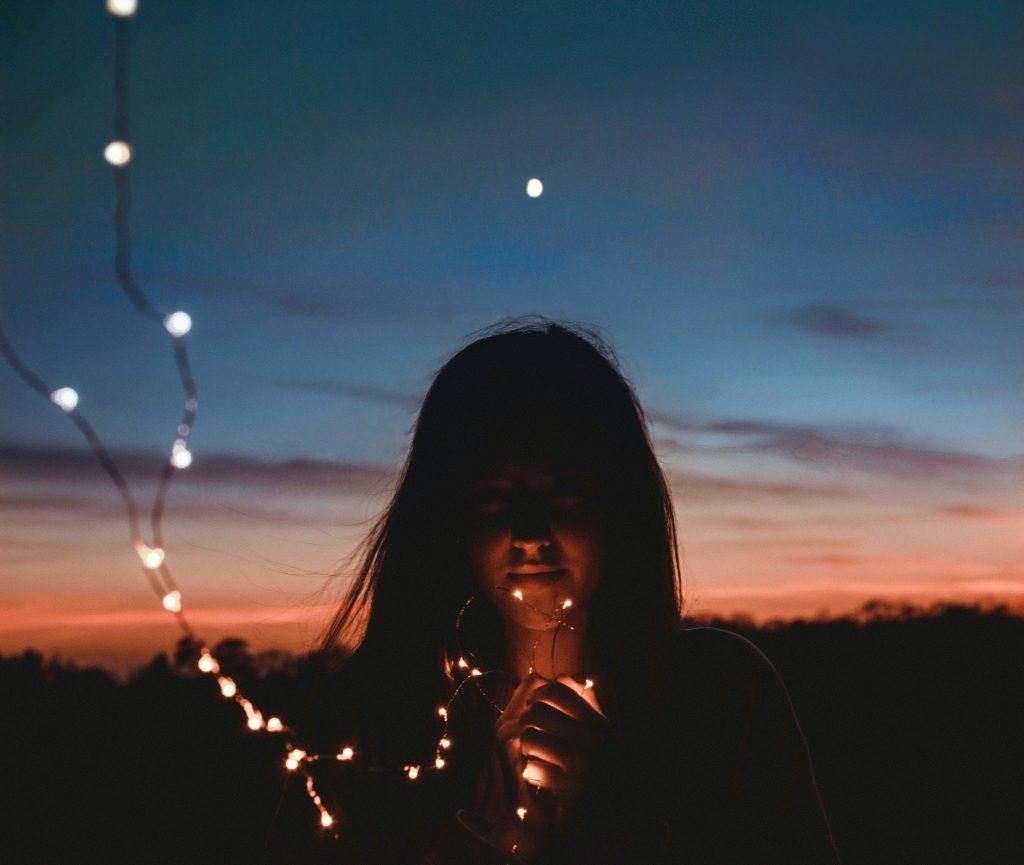 Mulher segurando pisca perto do rosto com céu escurecendo ao fundo