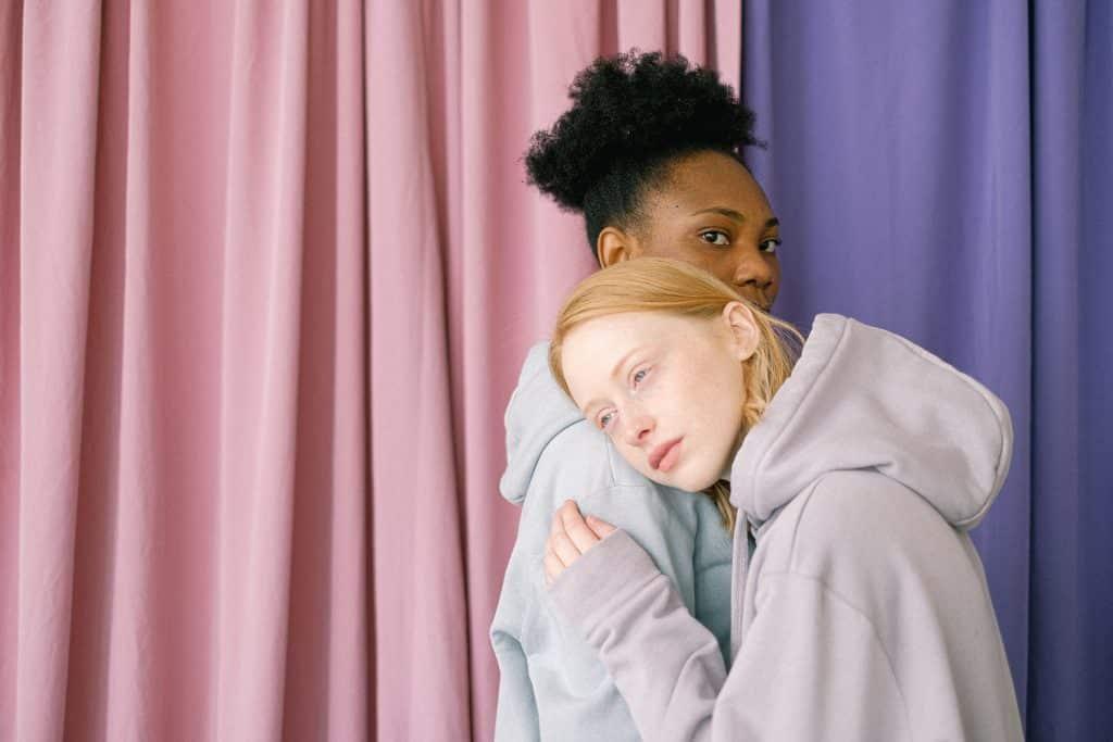 Duas mulheres abraçadas com expressão séria, em frente a uma cortina.